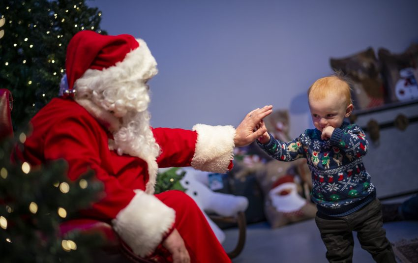 Father Christmas Hi Five with little boy in a festive jumber