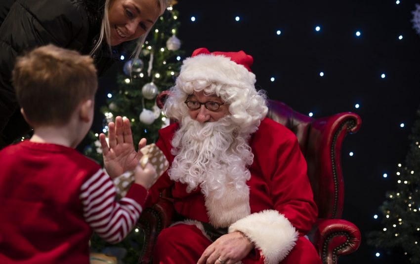 Father Christmas giving a gift to child in a red top