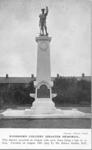 Black and white postcard image of Ashington Miners' Memorial. Front view. The memorial stands on a grassed lawn within Hirst Park, colliery housing visible behind a line of trees. Wording beneath the image reads: 'Clarance-Wilson, Consett / Woodhorn Colliery Disaster Memorial / This disaster occurred on August 13th 1916, there being a loss of 13 / lives. Unveiled on August 18th 1923 by Mr Robert Smillie, M.P.'