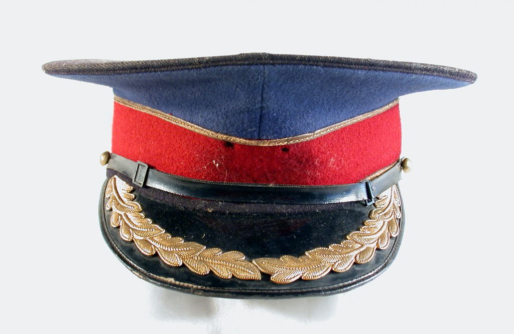 Ashington Colliery brass band jacket and cap. Peak cap is made from matching blue .and red wool finished with gold embroidery detailing. The visor is black and decorated with gold laurel wreaths.