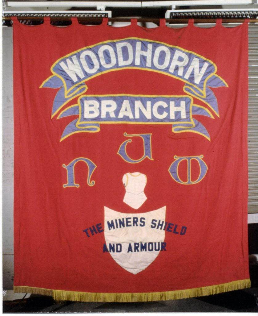 Woodhorn Colliery banner. Red silk with gold fringing. Reverse view; two blue scrolls with white lettering reads ' Woodhorn / Branch'. Below in miniscule script reads the acronym NUM above an image of plate armour and simple shield in silver above shield overlaid with the text 'The Miners Shield / and Armour'.