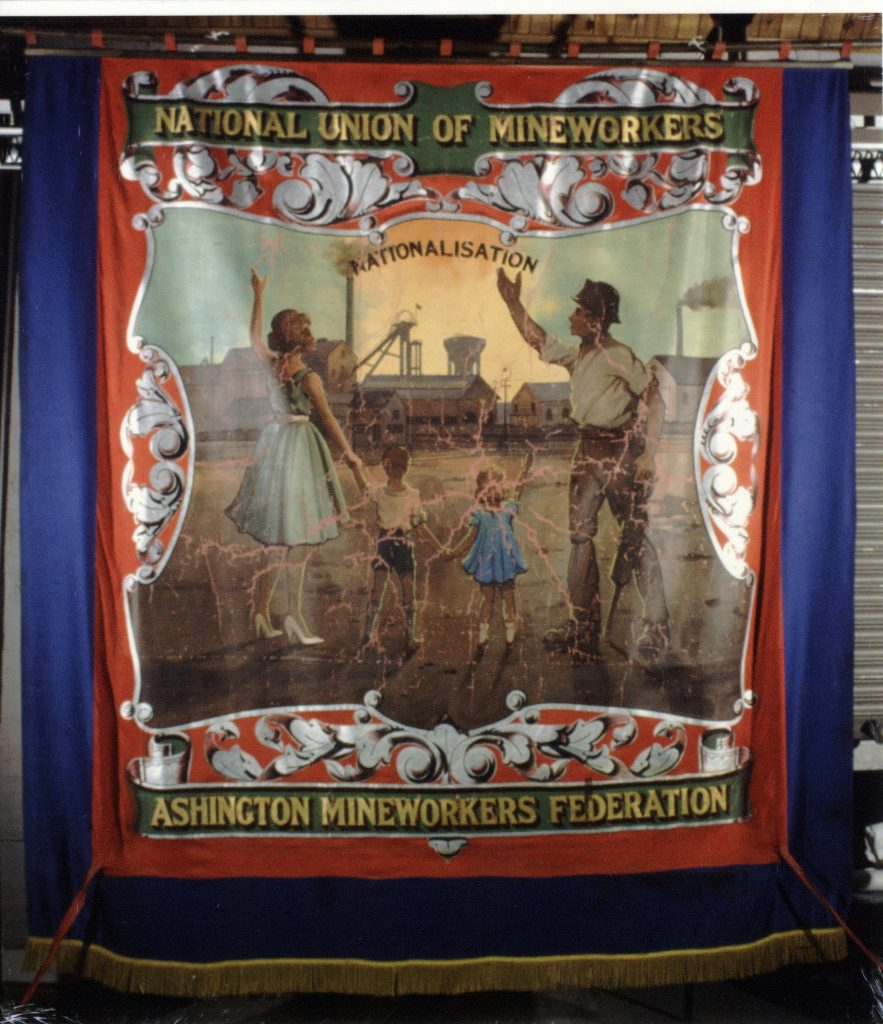 Ashington Mineworkers Federation banner. Blue and red silk painted with gold braid fringe. Obverse view; central image panel shows a family group dressed in smart, warm weather 1950s style clothing, arms outstretched in celebration (left to right, mother, son, daughter, father - in miner's helmet) in the foreground facing a colliery scene (unidentified). On the horizon the sun is rising. The words 'Nationalisation' hover over the scene. The image is surrounded by silver foliate border designs. The top scroll, in green and gold, reads 'National Union of Mineworkers'. The bottom scroll reads Ashington Mineworkers Federation'.