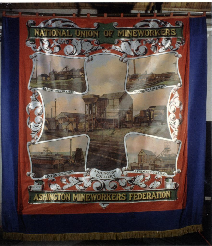 Ashington Mineworkers Federation banner. Blue and red silk painted banner with gold braid fringe. Reverse view; central image pane shows a group of collieries. Ashington Colliery is large central image, frames by four other collieries in the corners; from clockwise - Woodhorn Colliery, Lynemouth Colliery, Linton Colliery and Ellington Colliery. The image is surrounded by silver foliate border designs. The top scroll, in green and gold, reads 'National Union of Mineworkers'. The bottom scroll reads Ashington Mineworkers Federation'.