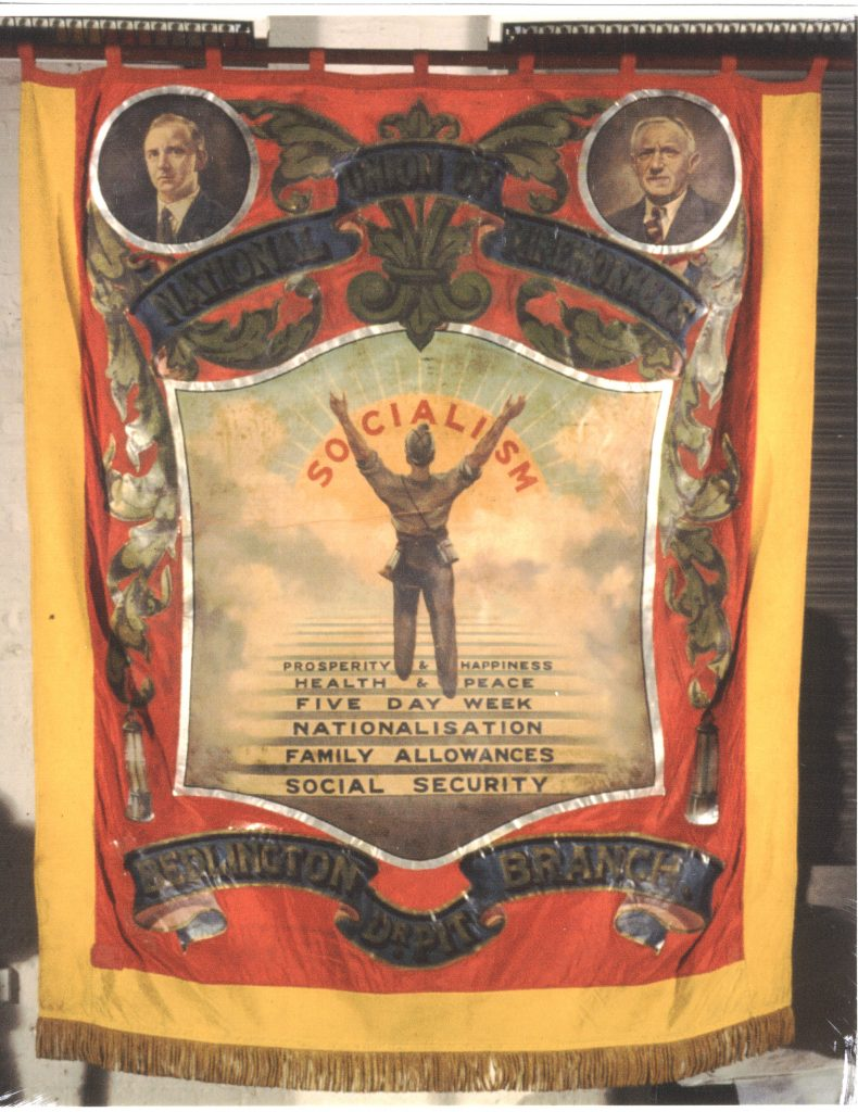Bedlington 'Dr Pit' banner. Yellow and red silk painted banner with gold braid fringe. Reverse view: an imagined sky scene, a miner, wearing a helmet and safety lamp, walks with his arms outstretched up a set of steps emerging from the clouds, (which read 'Prosperity & Happiness' 'Health & Peace' 'Five day week' 'Nationalisation' 'Family Allowances' 'Social Security') towards a sunrise overlaid with the text 'Socialism'. Additional details include two safety lamps hanging from the foliage and two roundels at the top right and left corners of the panel show male portraits. The top scroll, in blue and gold, reads 'National Union Mineworkers'. The bottom scroll reads 'Bedlington Dr Pit Branch'