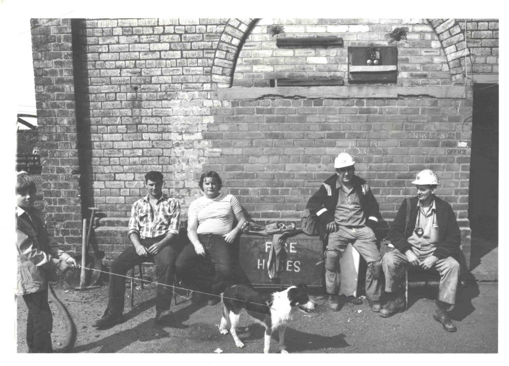 Obverse of a photographing showing men outside a building at Woodhorn Colliery dating to around the time of Woodhorn Colliery closure in 1981.